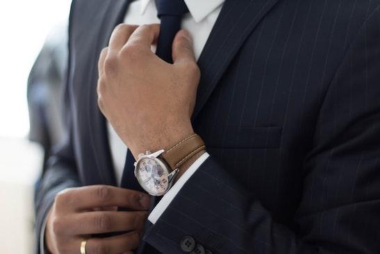 Vīrietis melnajā uzvalkā un ar pulksteni tur kaklasaiti