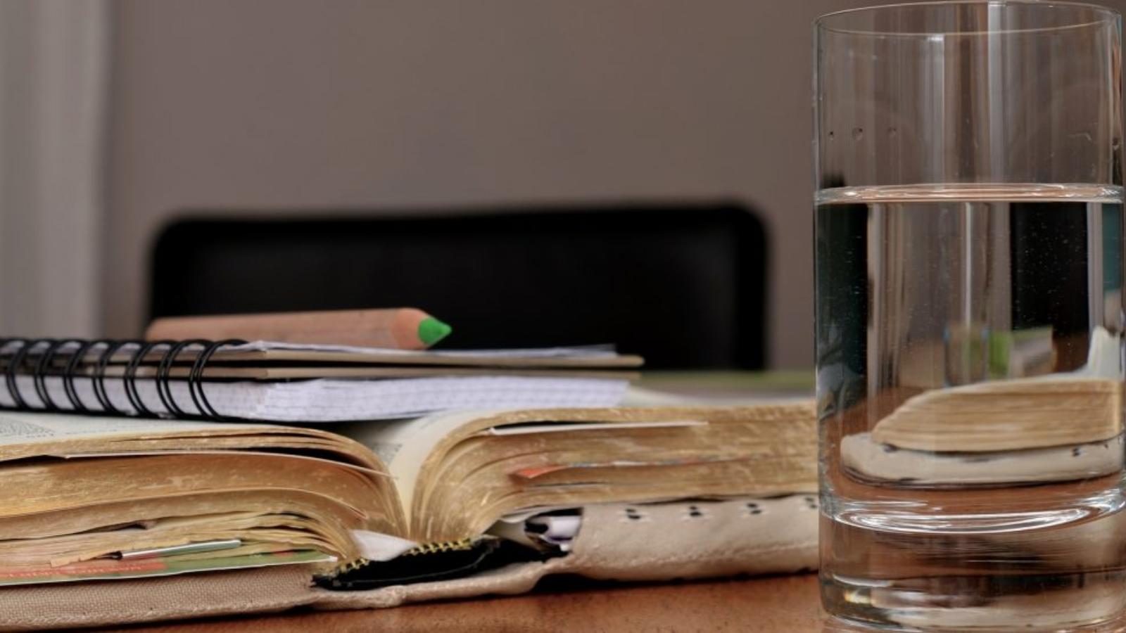Ūdens glāze pirmajā plānā un grāmata ar kladi un zīmuli, otrajā fonā.