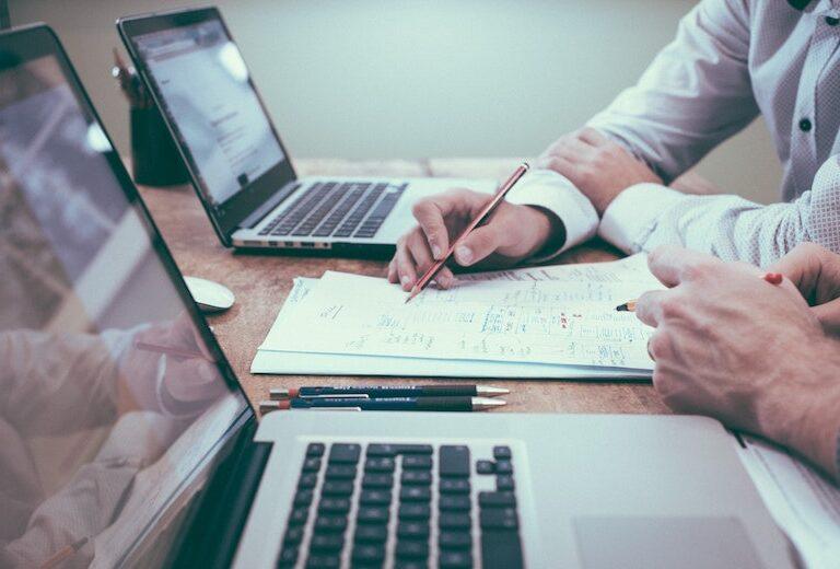 Vīrietis pie datora parāda ar zīmuli uz papīra citam vīrietim ar pildspalvu