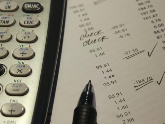 Kalkulators pa kreisi, papirs ar cipariem un pildspalva