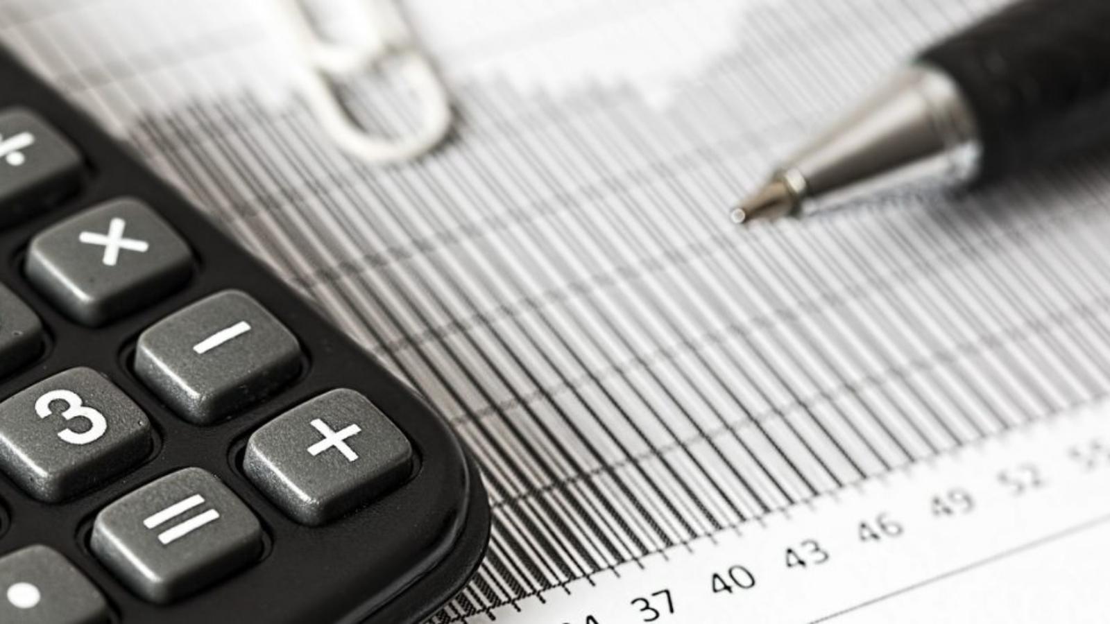 Melns kalkulātors, papirs un pildspalva