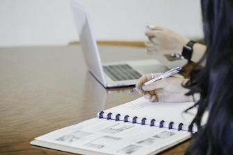 Divas sievietes pie galda sēž pie datora un pie burtnīcas